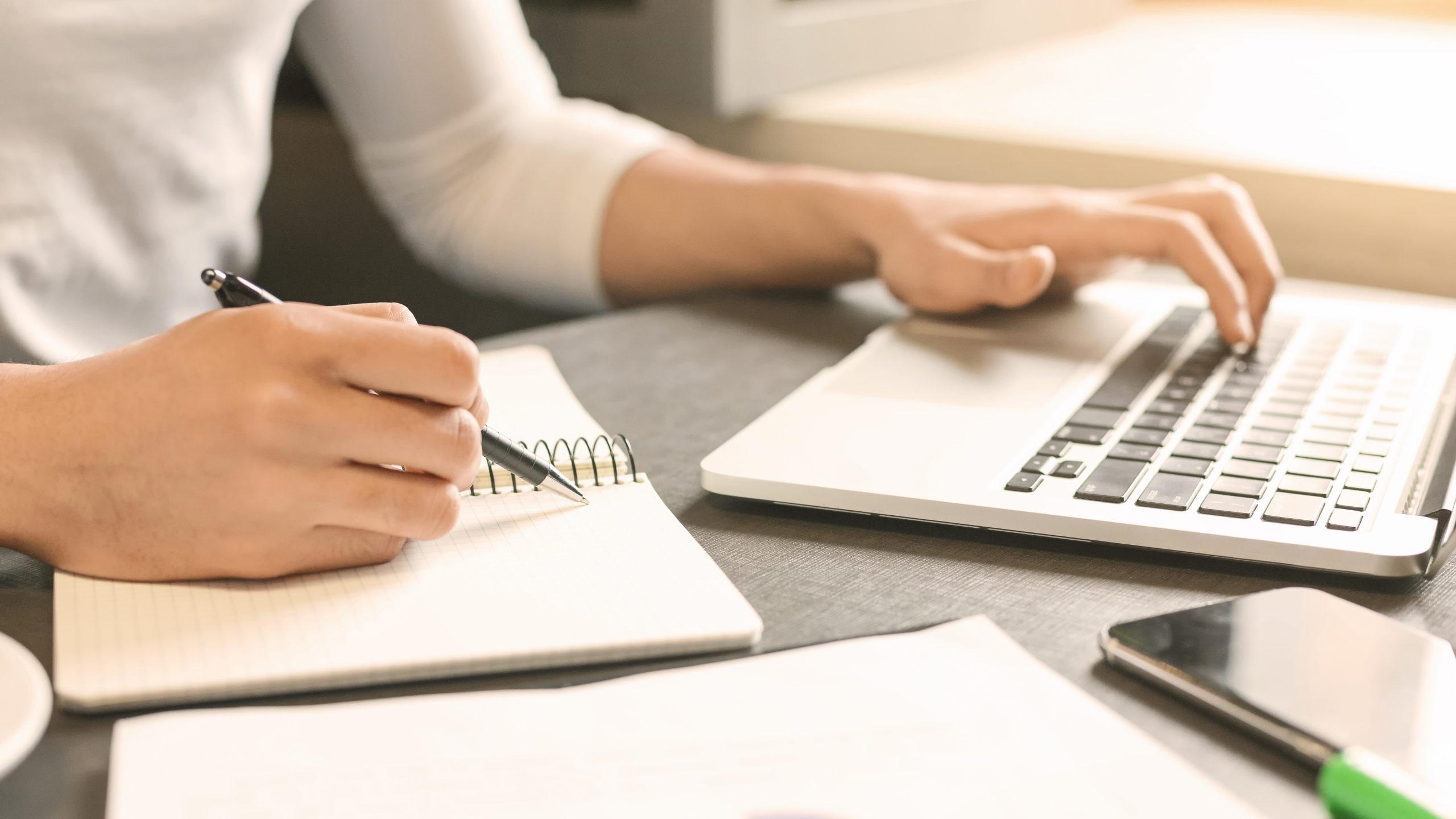 Personne utilisant son ordinateur et écrivant sur un cahier