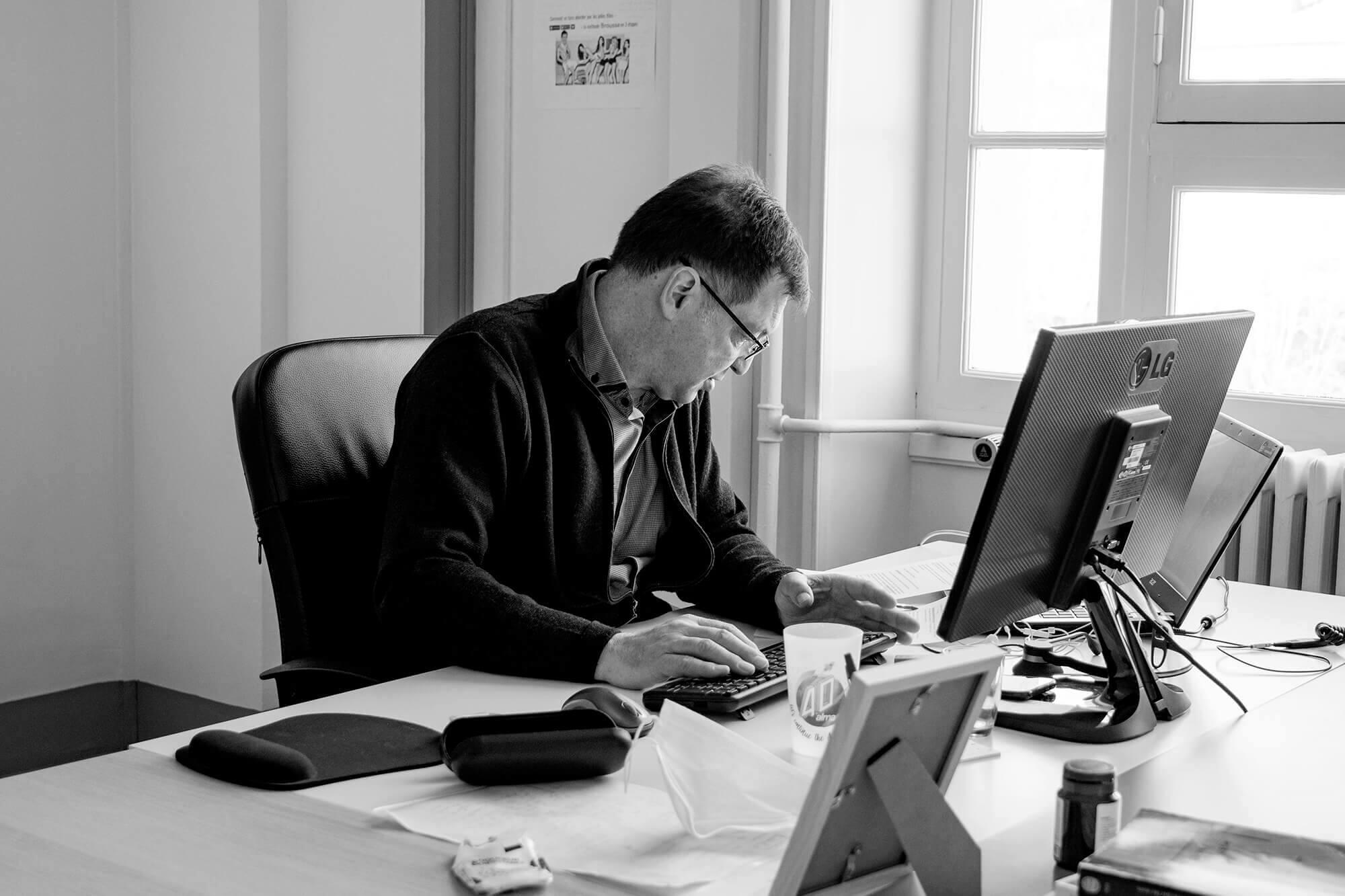 Homme en train d'écrire sur un ordinateur
