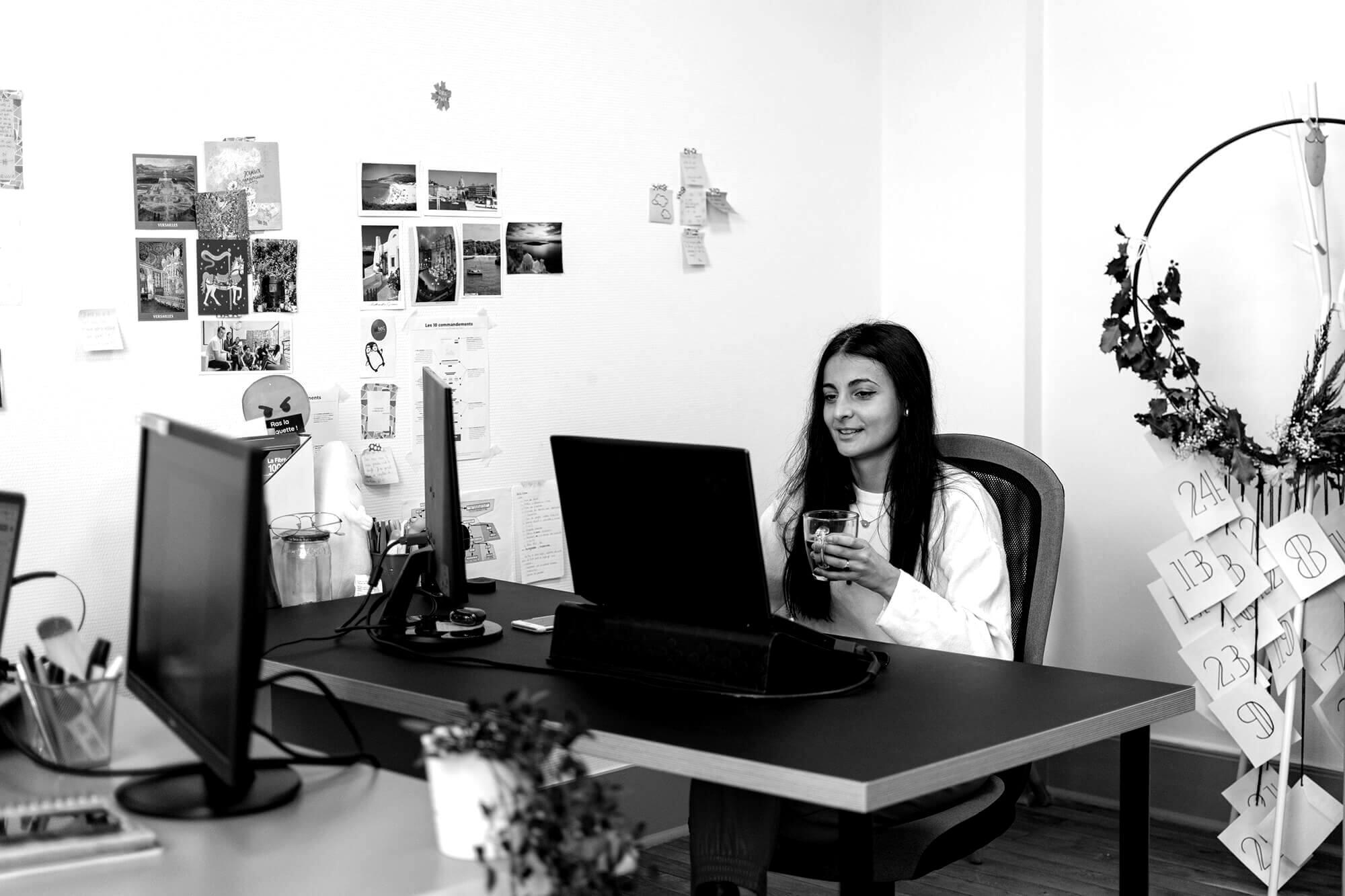 Jeune femme buvant un café en face d'un ordinateur