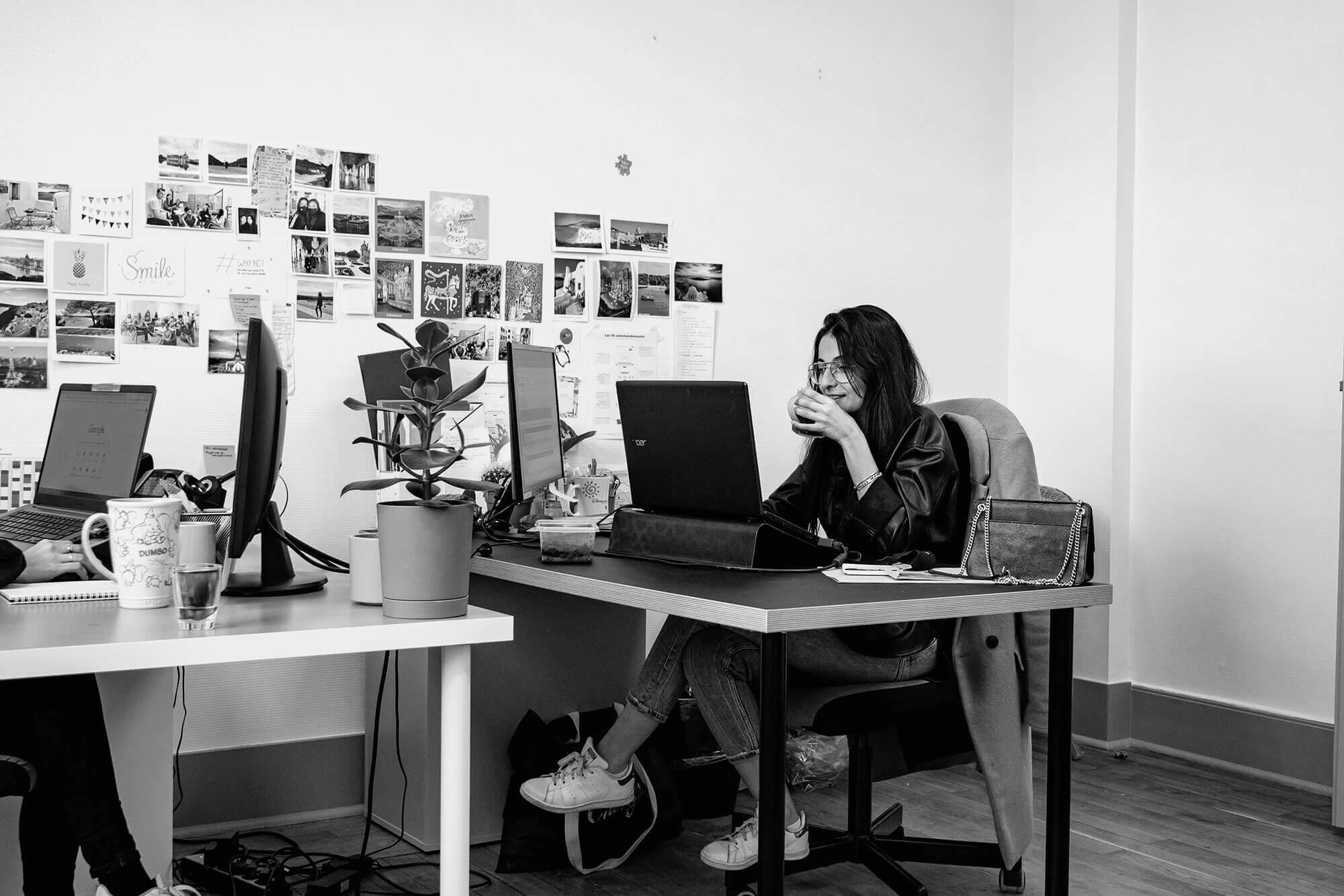 Jeune femme buvant un café devant un ordinateur