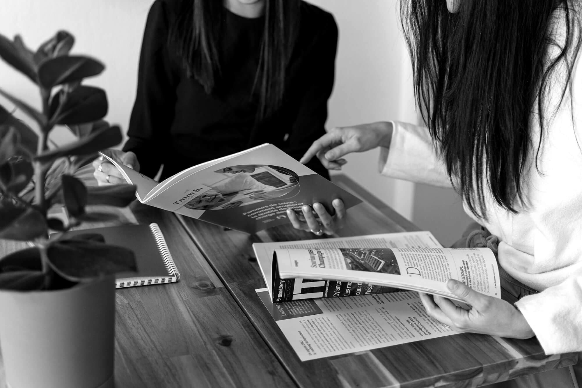 Deux personnes discutant de retombées presse IT autour d'une table