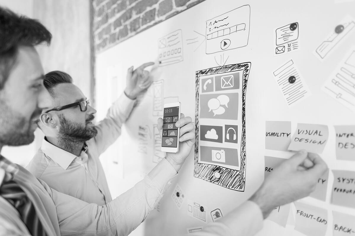 Collaborateurs discutant des critères d'un cahier des charges IT