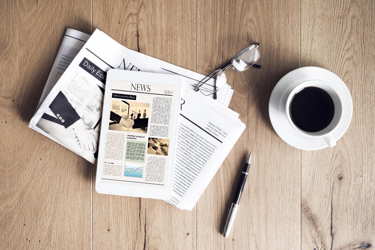 Affichage d'un communiqué de presse IT sur une tablette et un journal