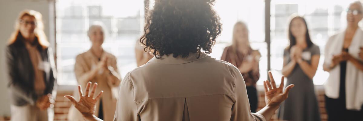 Femme parlant à un groupe de personne debout