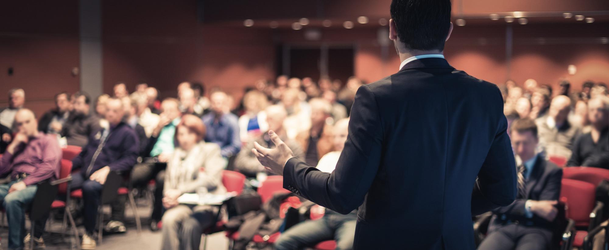 Vue de dos d'un homme en train de présenter des informations à un auditoire