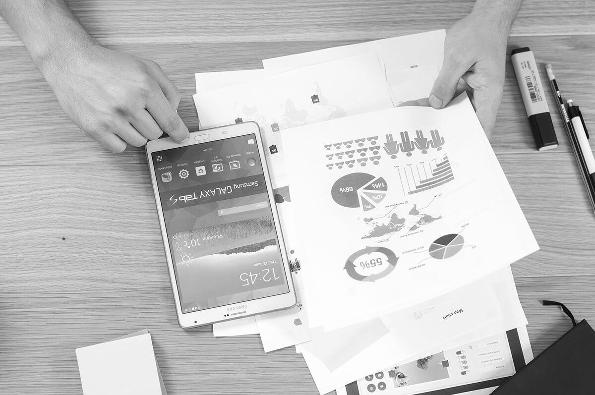 Personne consultant une feuille de statistiques posée près d'un smartphone