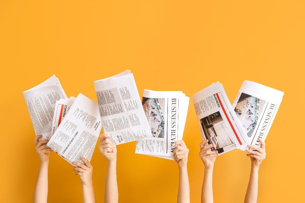 Mains levées tenant chacune un journal