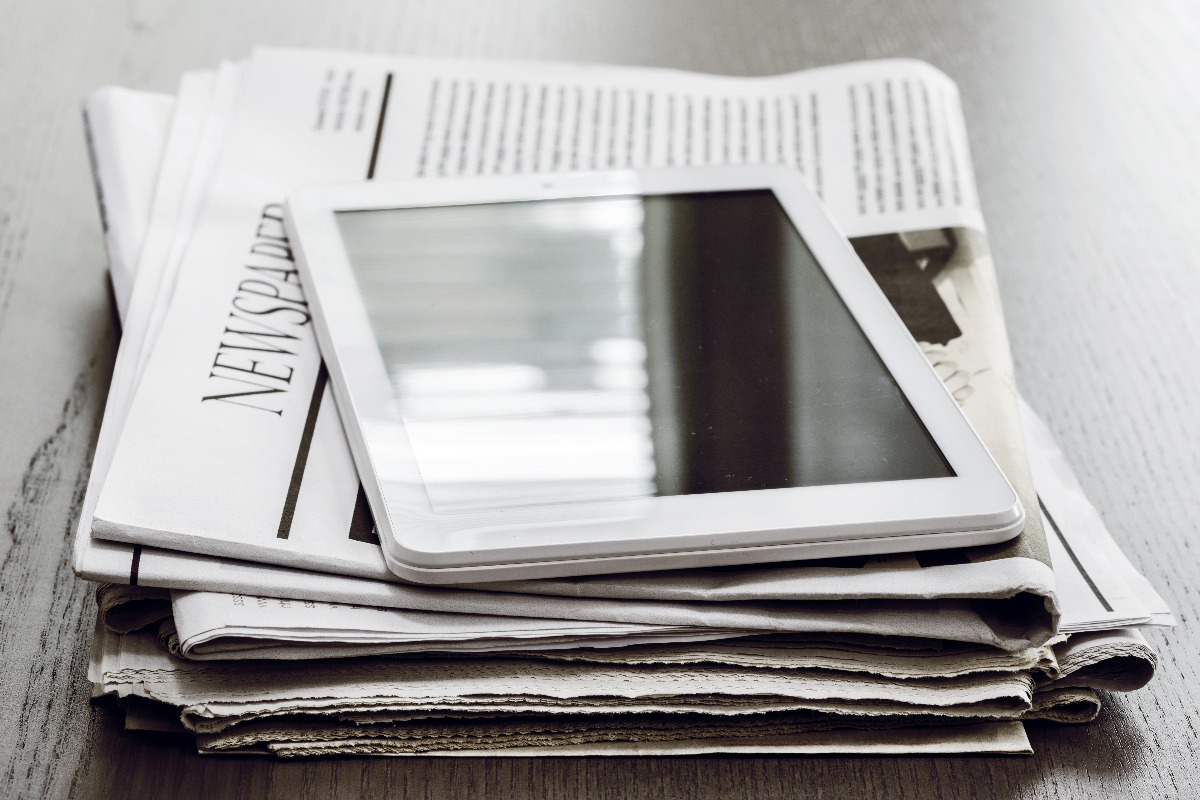 Tablette posée sur un journal plié
