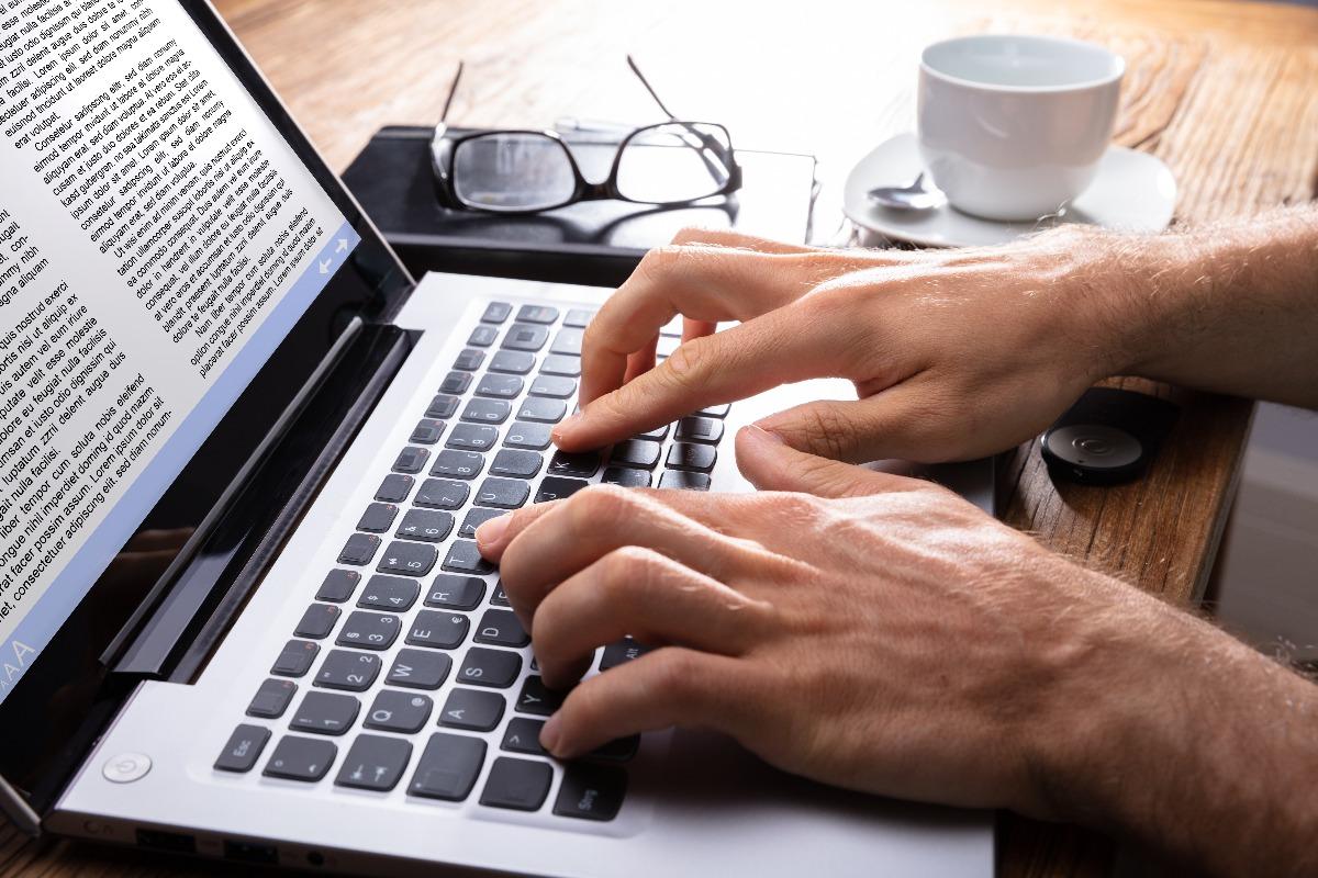 Personne écrivant sur son ordinateur avec des lunettes et une tasse de café posées à côté