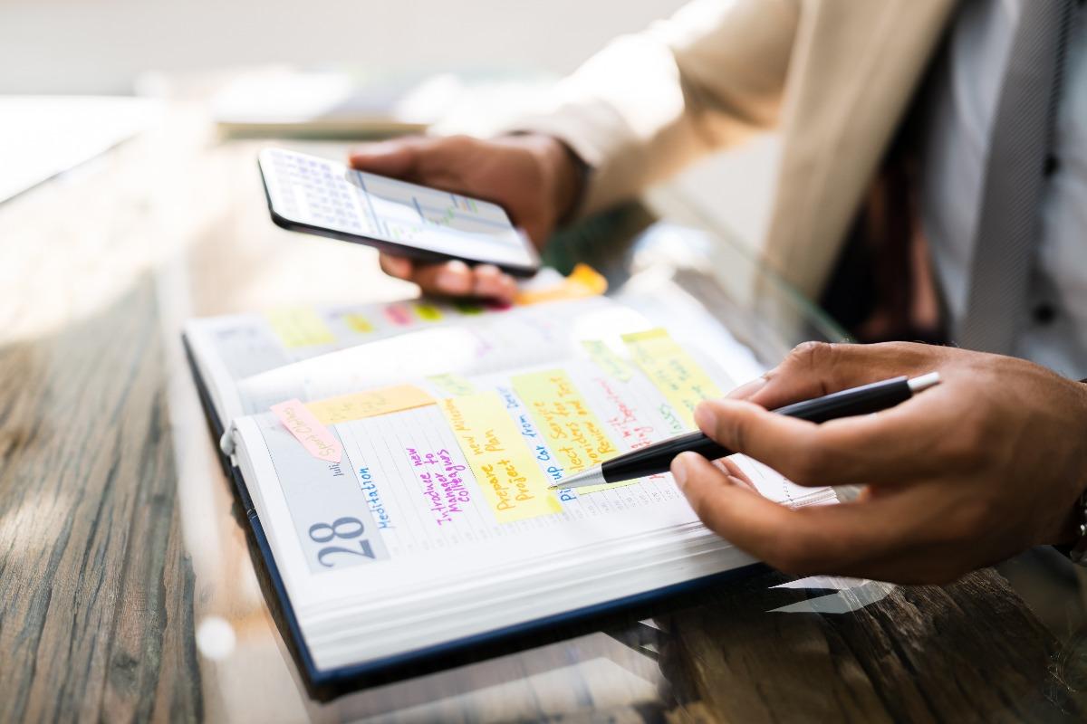 Personne utilisant un agenda et un smartphone
