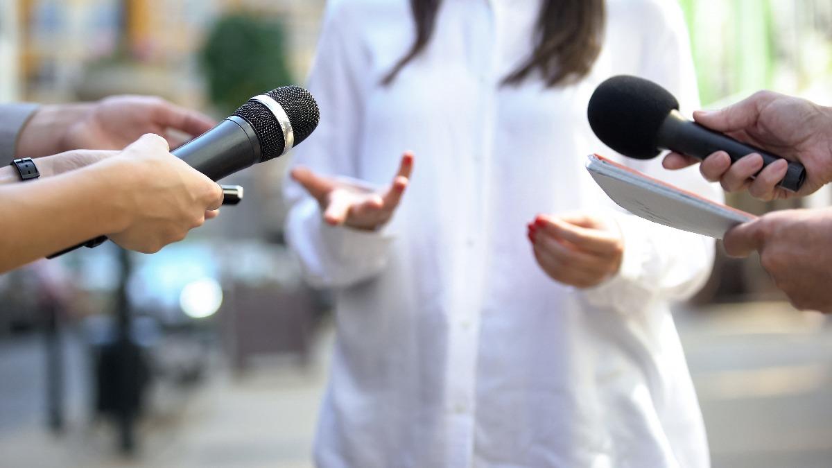Personnes tendant des micros vers une dame répondant à des questions