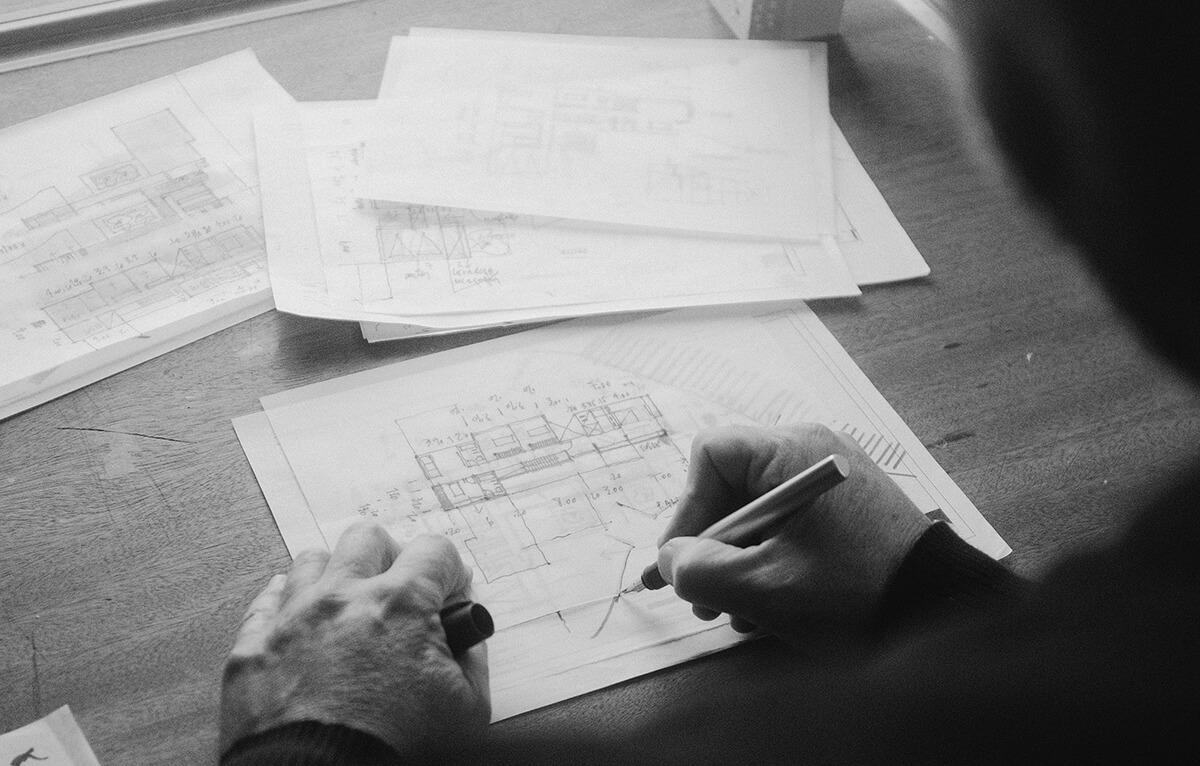 Homme dessinant un plan détaillé avec un stylo