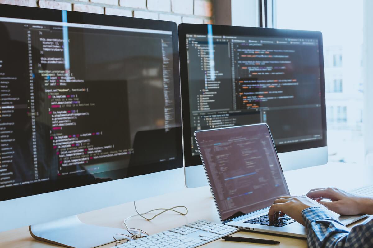 Développeur utilisant 3 écrans pour concevoir un site internet