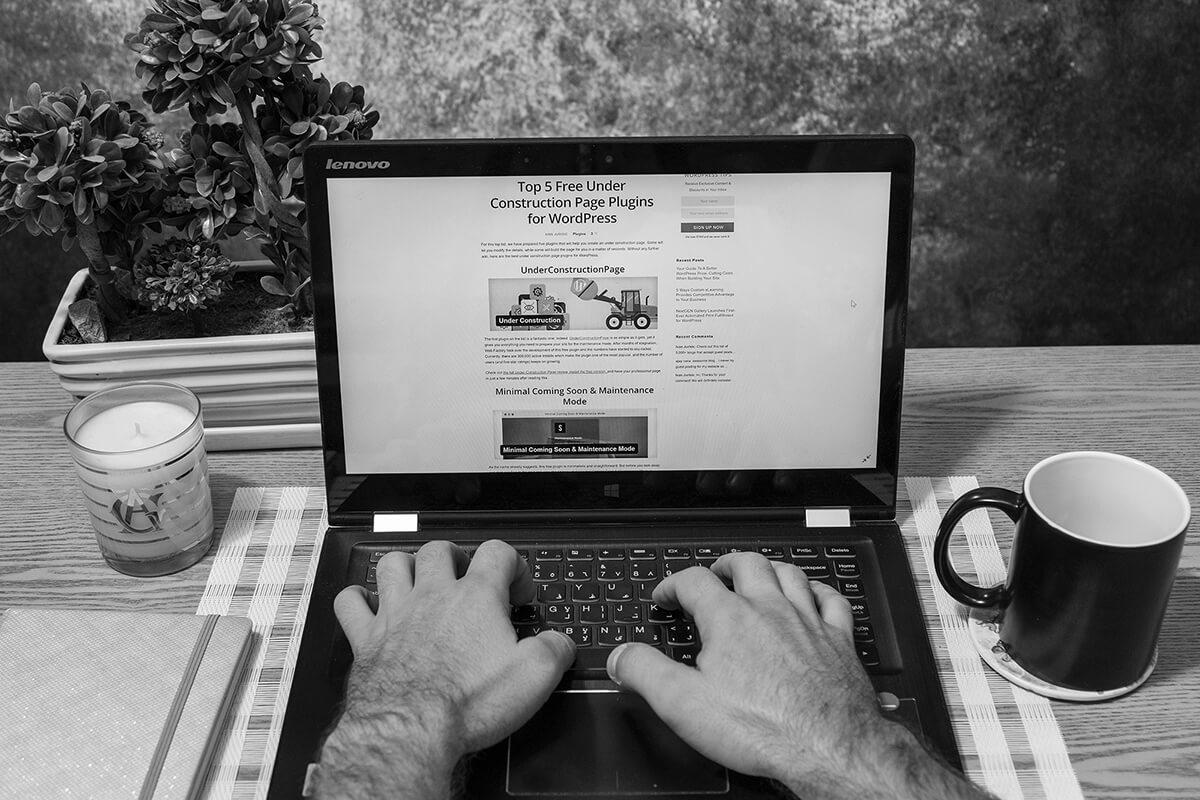 Personne utilisant son ordinateur pour lire des articles