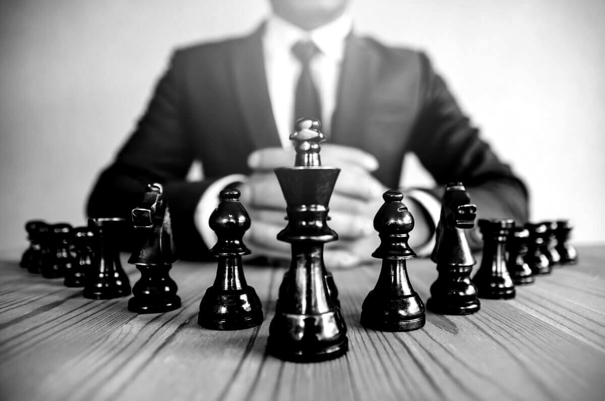 Homme en costume assis derrière les pièces d'un jeu d'échec